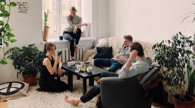 Group of happy people sat on chairs and sofas at home