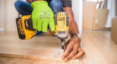 man fitting floorboards during a house remodelling project
