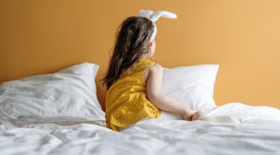 Yellow bedroom walls with child in a yellow dress sat on a white bed
